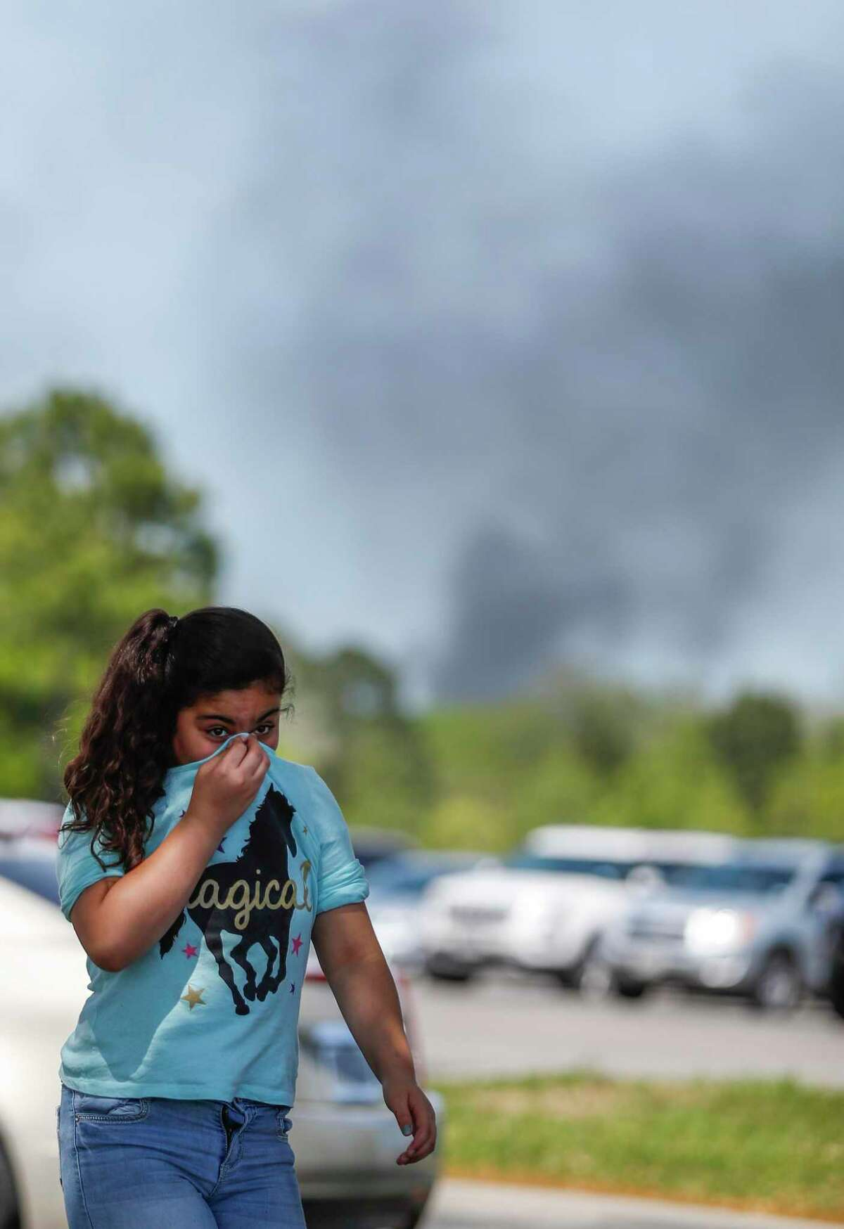 A little girl covers her nose as she and her family come to pick up a family member from the Crosby Kindergarten Center as the plume from the KMCO fire, billows in the backround, on April 2, 2019, in Crosby.