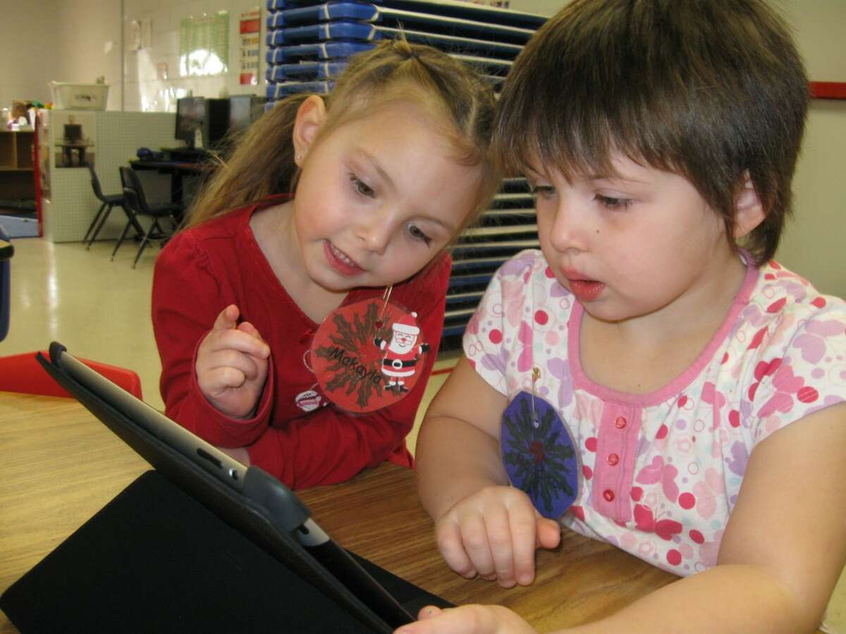 FiveCAP Head Start students Makayla Kenny and Maddison Eble use one of the iPads in their classroom.