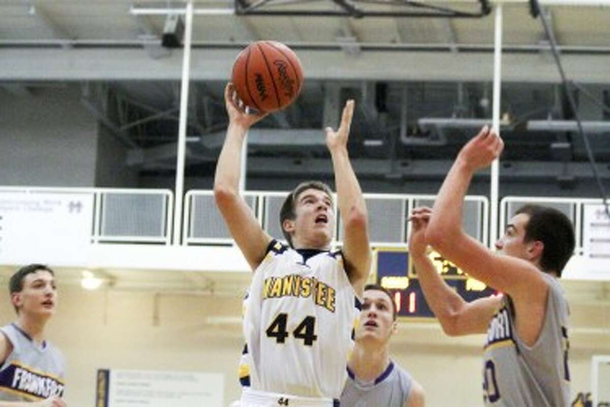 Manistee senior Dustin Simmons (44) shoots over Frankfort's David Loney (right) during the first half of Tuesday's game. (Matt Wenzel/News Advocate)
