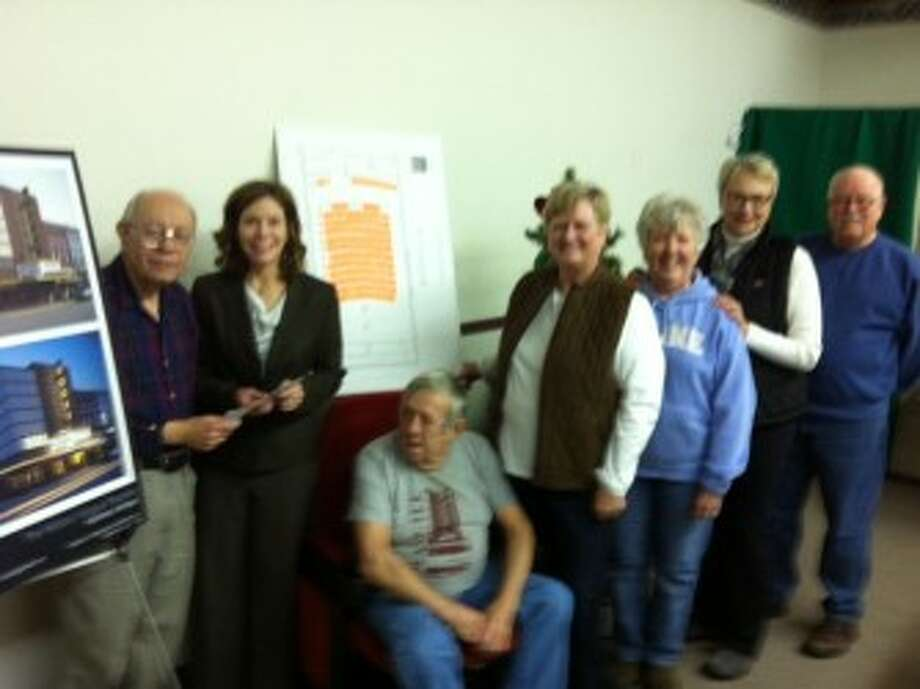 From left to right) Ken Holm presenting the check to Laura Heitzelman, director of the Manistee County Community Foundation, Jack Staffeld (seated), Celia Lumley Neitzke, Beverly Madeley Peralta, Maggie Dorfeld Voelker, and Alan Verheek.