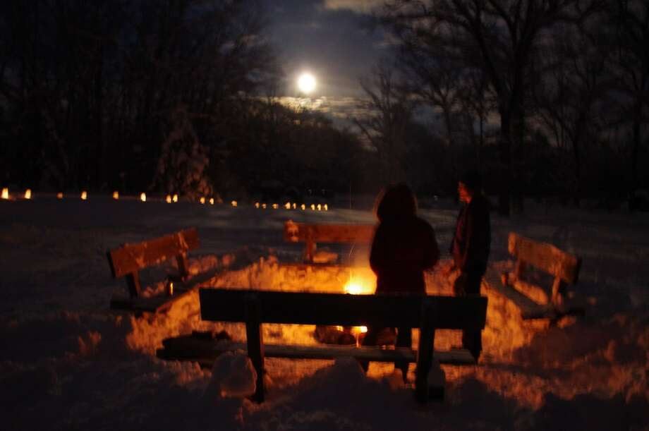 Skiers warm up at the outdoor fire pit as the moon rises over the Big M Cross Country Ski Area near Wellston. (Dave Yarnell/News Advocate)