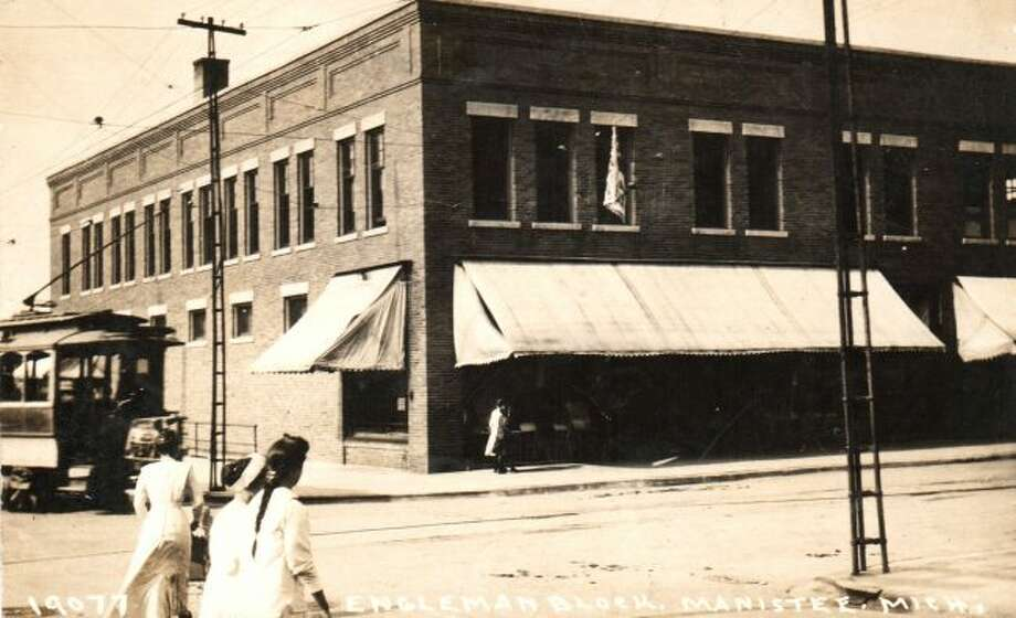 After the three story Engelmann Building that was located at the corner of Maple and River streets was destroyed by fire in the early 1900s it was replaced with a two story structure that is shown in this photograph with a cable car passing in front of it. The building is currently the home of Glik's.