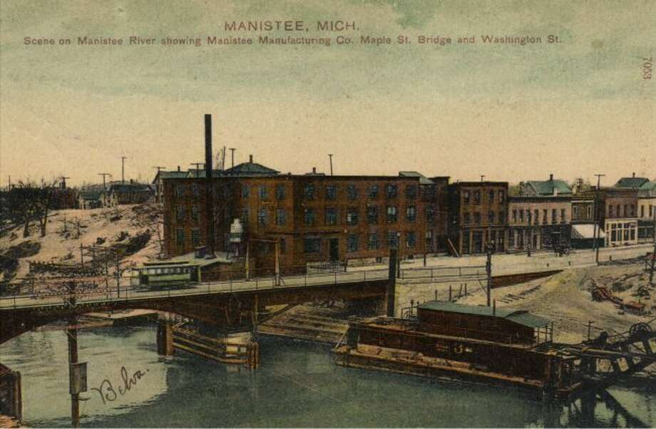 This late 1890s picture shows the Manistee River with the Manistee Manufacturing Company and the Maple Street Bridge with a trolley going across it.