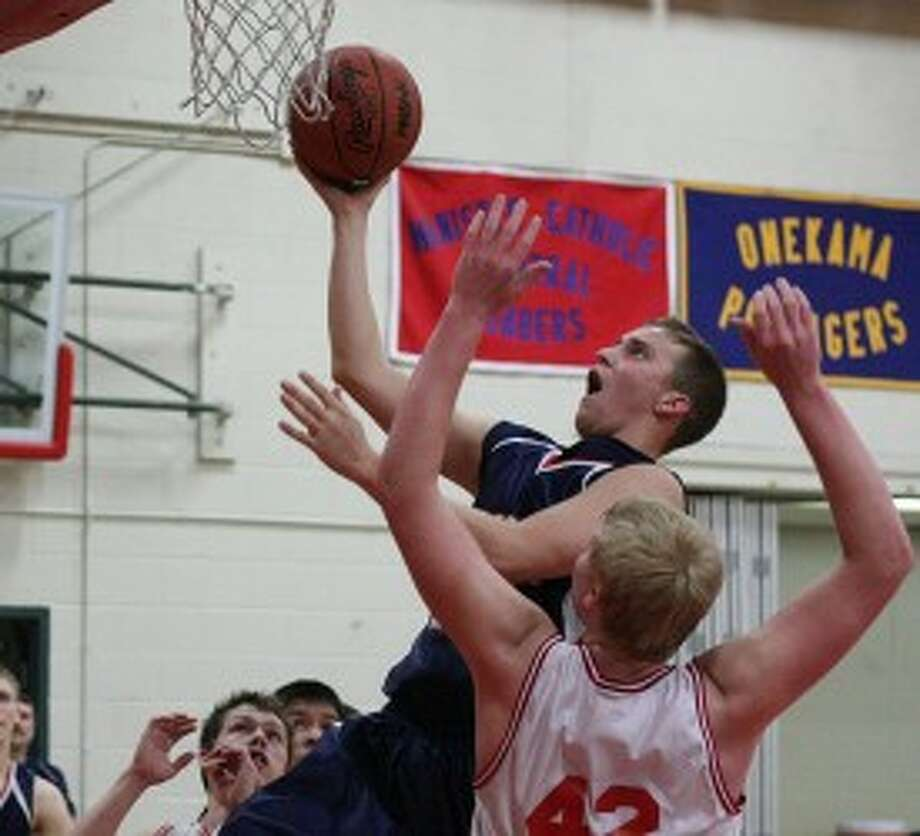 Manistee Catholic Central's Zack Bialik elevates for a shot in front of Mason County Eastern's Jimmy Appledorn (42) during Wednesday's game. (Dylan Savela/News Advocate)