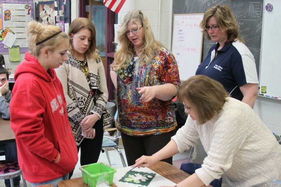 Michigan Legacy Art Park Education director Patricia Innis and Brethren High School Art teacher work with students under a program the school is running with area artists through a grant from the Michigan Council for Arts and Cultural Affairs.