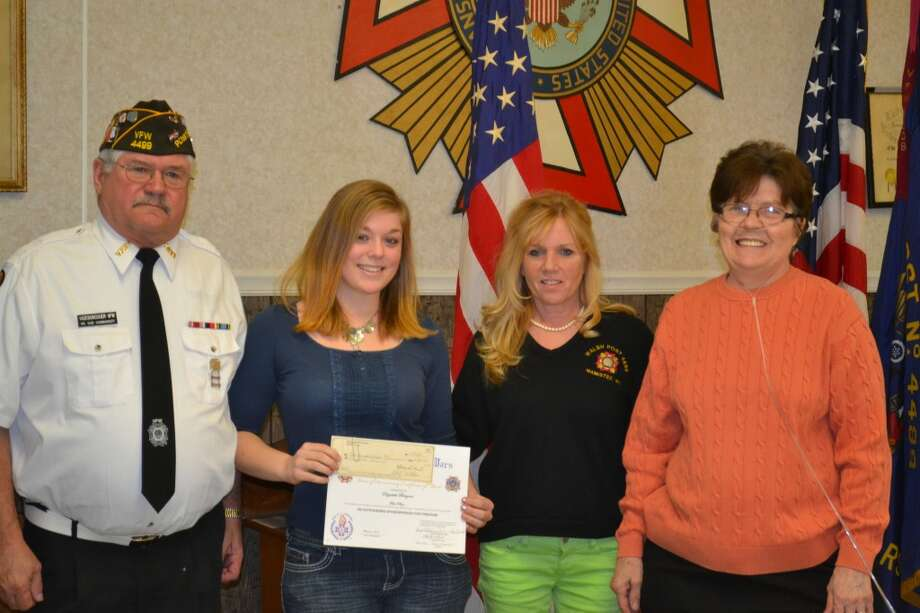 """From left, Don Vadenboncoeur, commander of the Manistee VFW post; Elizabeth Bergren of Onekama High School, who won first place in the """"Voice of Democracy"""" essay contest; Colleen MacDonald, VFW Ladies' Auxiliary president; and Cecilia Guenthardt, chairman of """"Voice of Democracy/Patriots Pen"""" (Meg LeDuc/Manistee News Advocate)"""