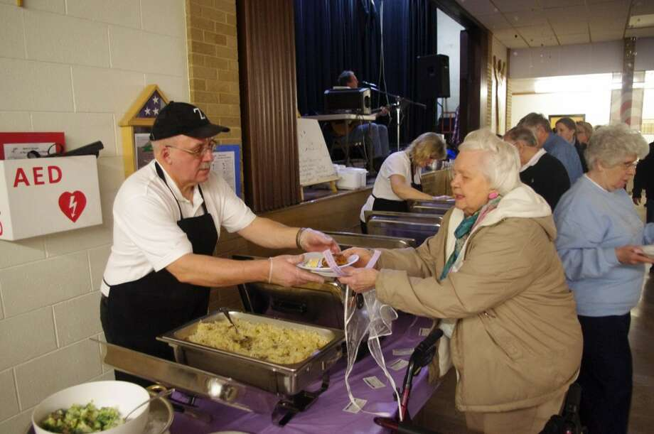 Jerry Zupin of Zupin's Catering hands a plate to Florence Rutowski. (Dave Yarnell/News Advocate)