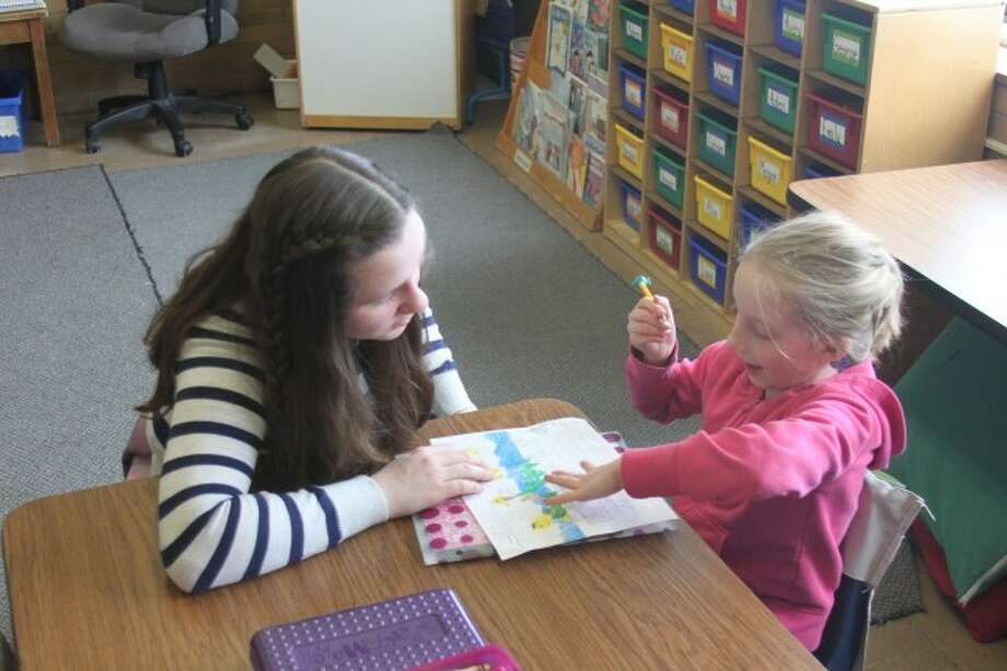 Jefferson Elementary School first grade student Brooke Myers works with Manistee Middle School student Nicole Weaver on improving her language skills. Myers had cochlear implants and is now learning to speak words she formerly would sign. The two students formed a special bond when Weaver came over to work on the Service Learning project.
