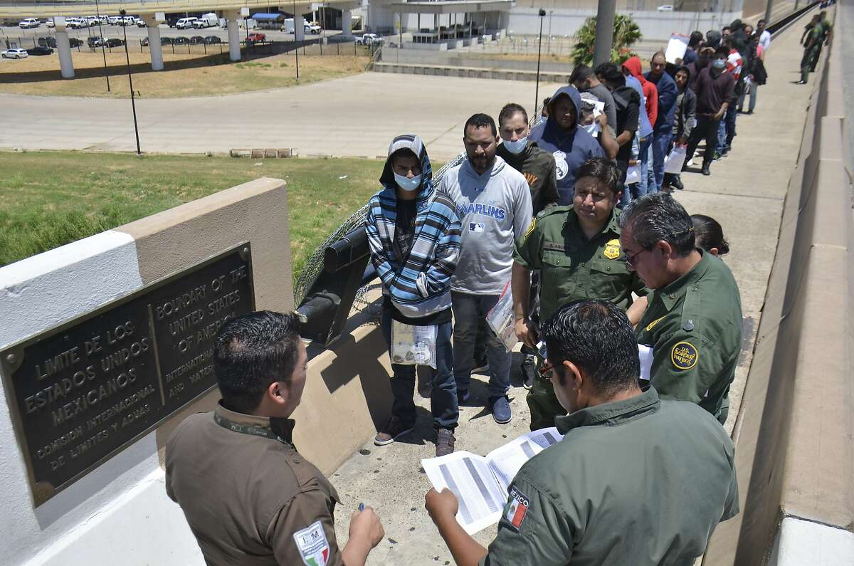United States Border Patrol officers return a group of migrants back to the Mexico side of the border as Mexican immigration officials check the list, in Nuevo Laredo, Mexico, Thursday, July 25, 2019. Mexico has received some 20,000 asylum seekers returned to await U.S. immigration court dates under the program colloquially known as