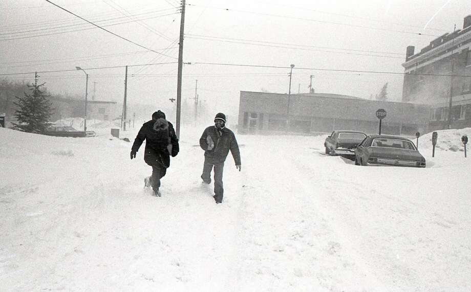 Two citizens walk west on Water Street during the great blizzard of January 1978. (Courtesy Photo/Manistee County Historical Museum)