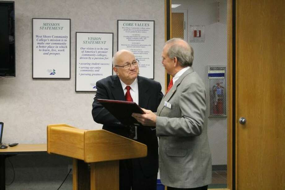 West Shore Community College Board of Trustees chair Bruce Smith (left) presents Mike Ennis with the proclamation he read at Monday's board meeting. The meeting was the last for Ennis who is retiring from the board after 20 years of service.
