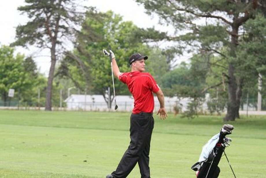Manistee Catholic Central senior Zack Bialik lets go of his club after his approach shot on the second hole of a playoff in the Division 4 state finals at Forest Akers East on Saturday. (Matt Wenzel/News Advocate)