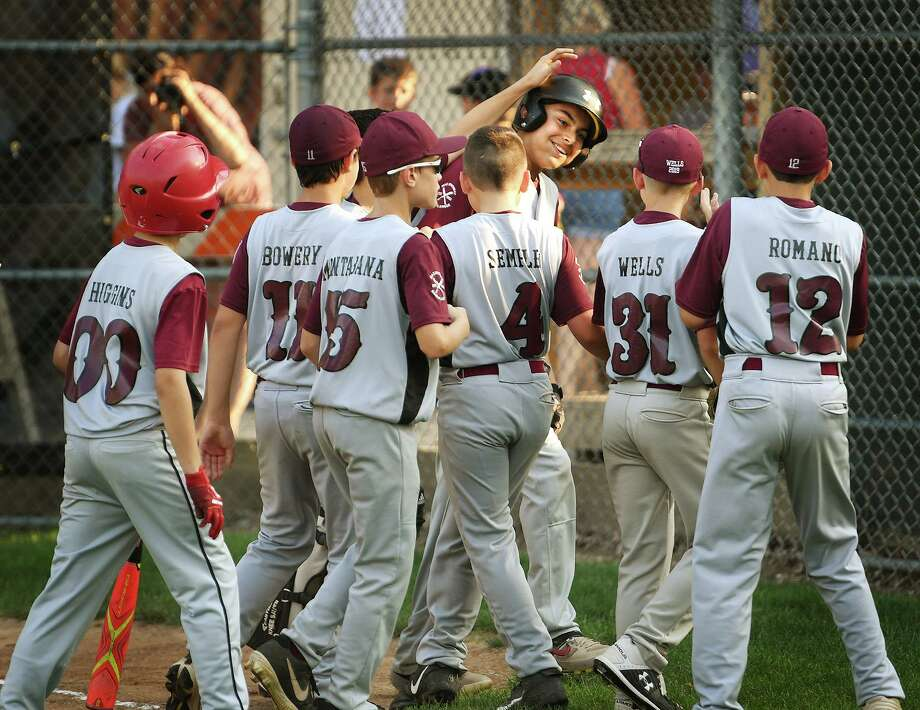 Max Sinoway's Nate Acevedo is mobbed at home plate by his teammates after hitting a two-run home run in the first inning of their win over Simsbury on Monday. Photo: Brian A. Pounds / Hearst Connecticut Media / Connecticut Post