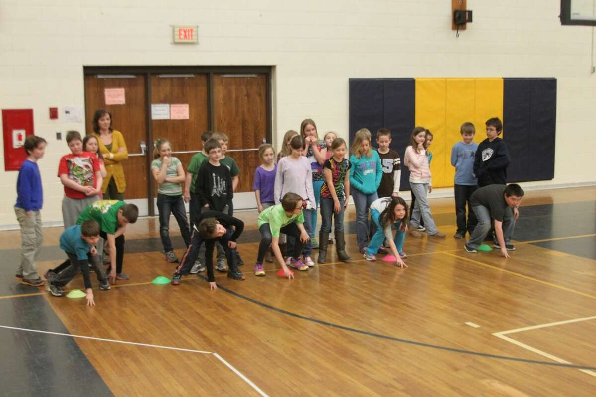 Students take part in a drill that brings them out of a football stance to do a short sprint.