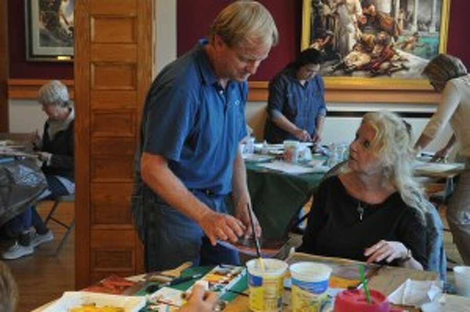 During a Manistee Art Institute watercolor workshop on Monday, artist Nathan Greene worked with several Manistee-area students, teaching color, composition, design and more. Pictured is Greene working with Patricia Rubright.