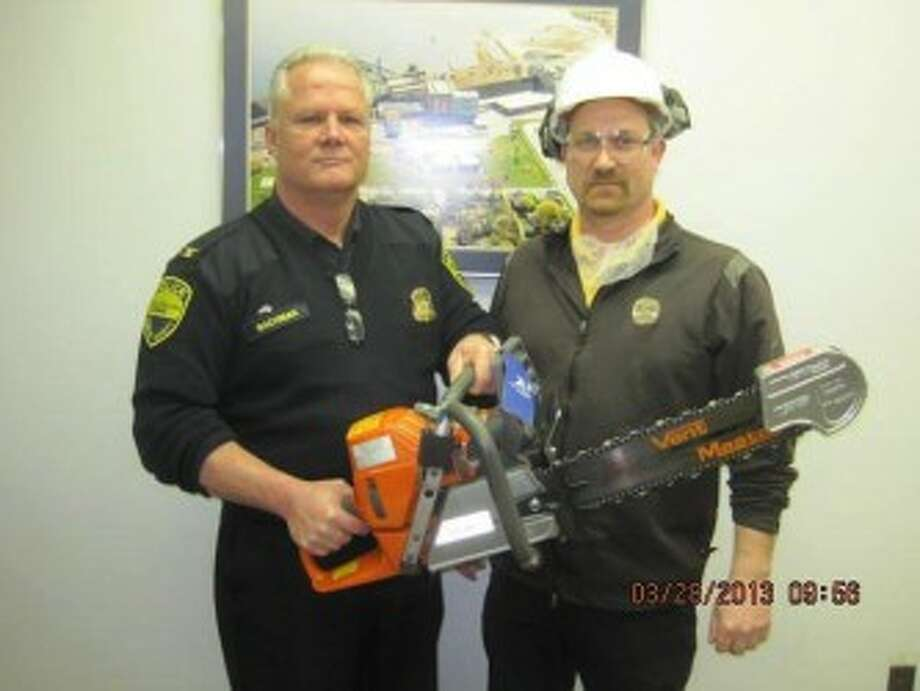 Manistee public safety director Dave Bachman shows off the saw donated by Morton Salt. Also pictured is Jacob Bialik of Morton Salt.