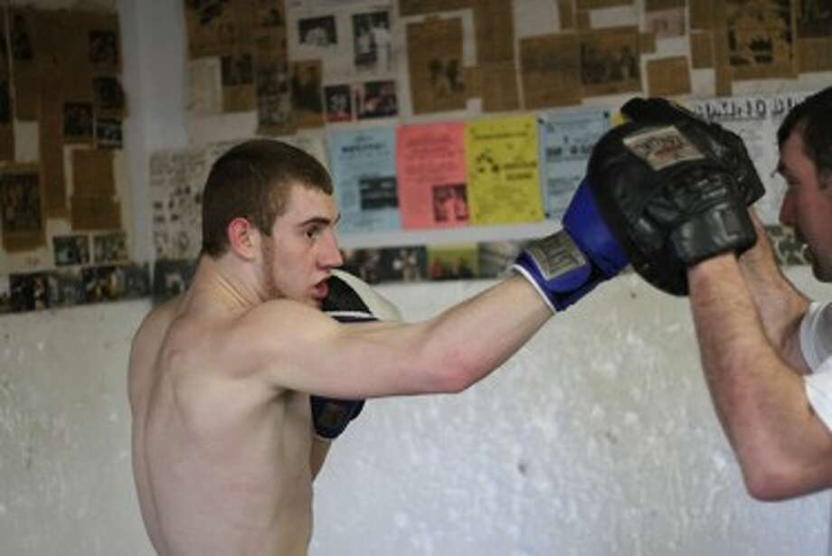 Manistee Boxing Club's Tyler Bussell trains with his father Steve Bussell on Thursday. (Matt Wenzel/News Advocate)