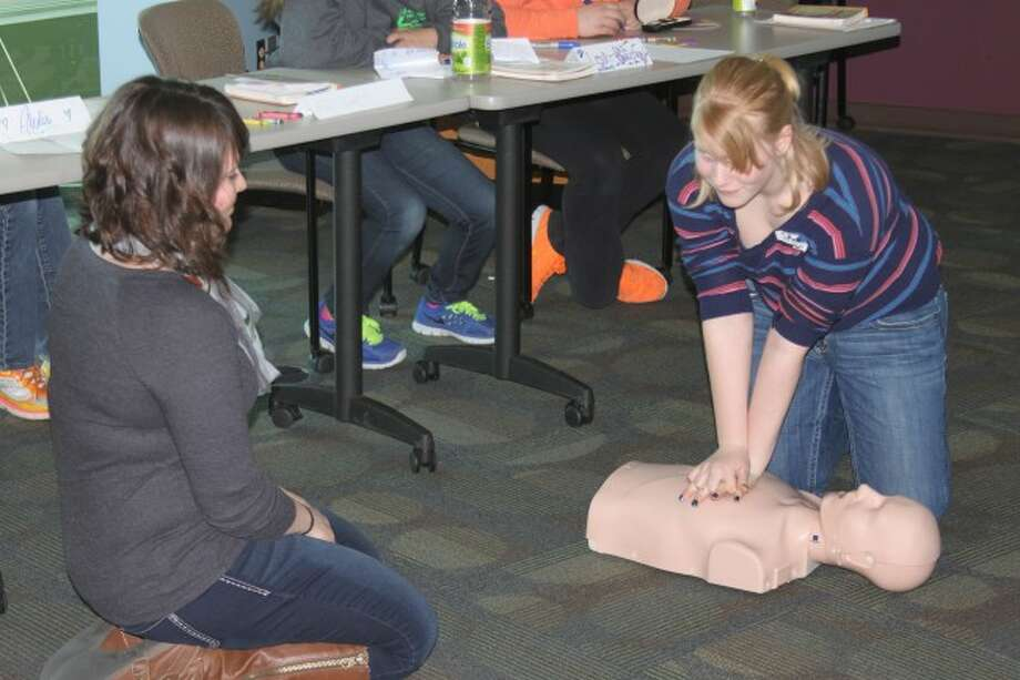 Instructor Lisa Cooper keeps a watchful eye over a student learning CPR during the West Shore Community College Babysitter training class.