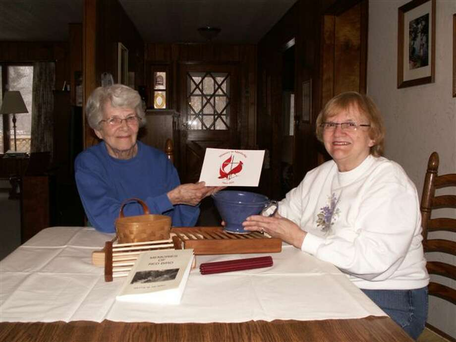 Mary Glover (left) and Betty Jo Riggs, co-presidents of United Methodist Women, look at articles to be sold at the Appalachian Craft Show and Bake Sale on April 20 at the Manistee United Methodist Church. (Courtesy Photo)