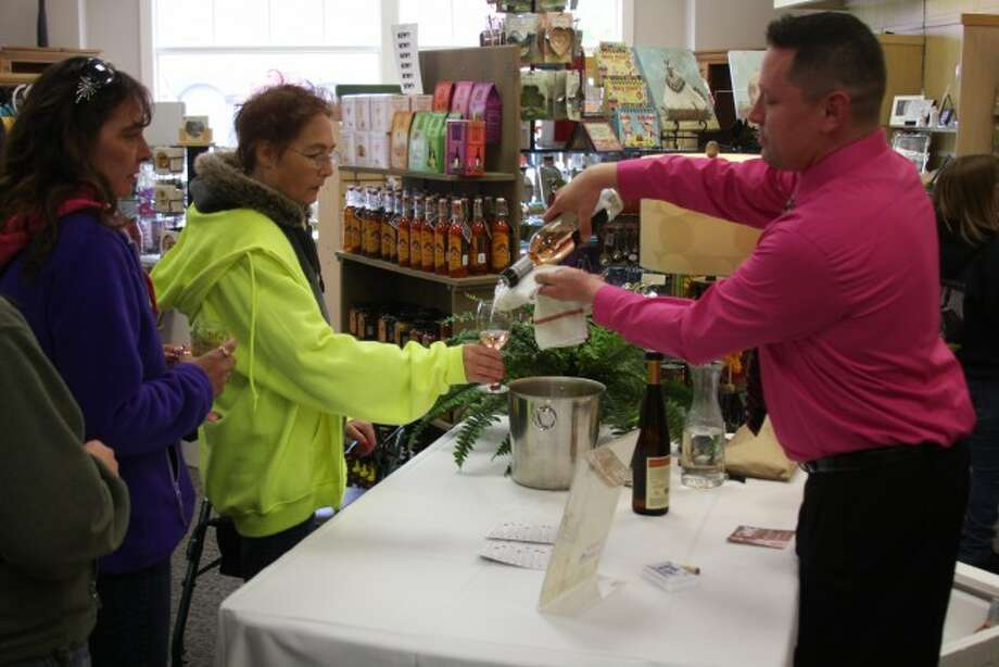 The Manistee Downtown Development Women's Wine and Chocolate Walk drew large crowds to the River Street area on Saturday. The event was designed to bring people to the downtown area. Shown are women lining up at Kellie's Hallmark to test wines from Chateau Grand Traverse and 2 Lads Winery.