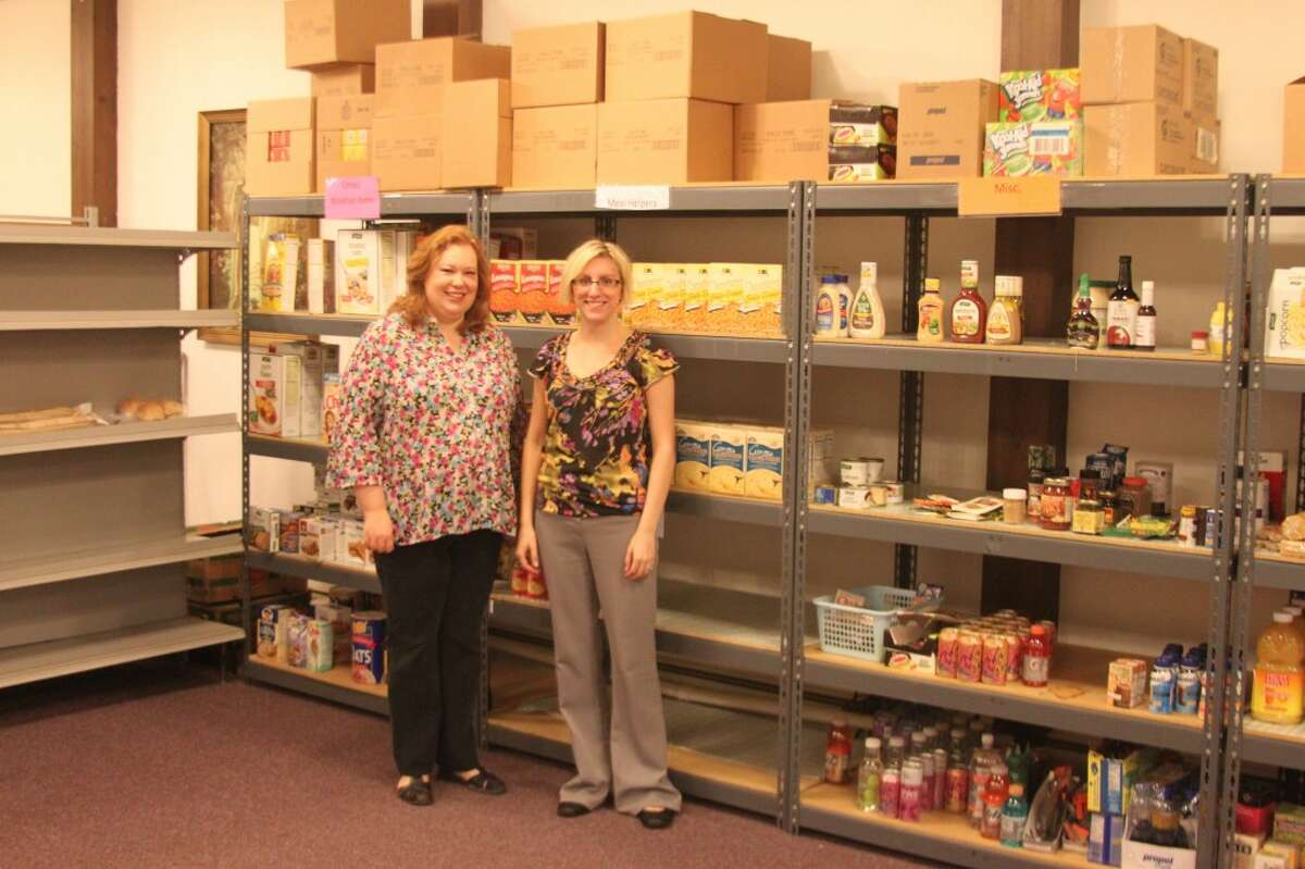 Salvation Army Social Services Case Worker Martie O'herron and office administrator Janelle Adamczak-Vandervest pose in front of the food pantry at the Salvation Army. The local offices have undergone a great deal of change, but they still offer full social services programs.(Ken Grabowski/News Advocate)
