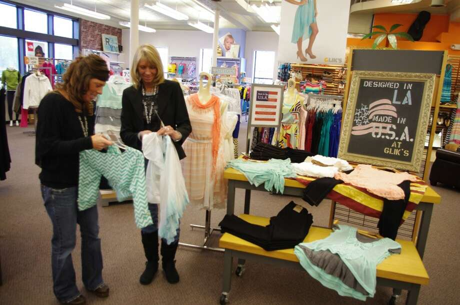 """Glik's staff members Michelle Sowa (left) and Becky Rabidue check out some of the """"Made in the U.S.A."""" collection at the store. (Dave Yarnell/News Advocate)"""