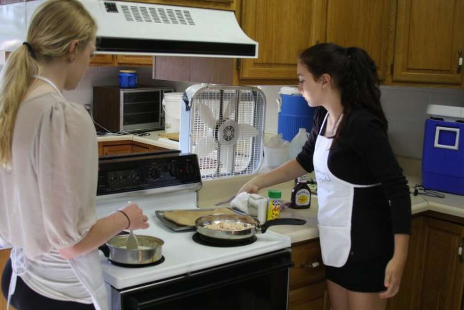 Brethren High School students Megan Wayward and Brittany Dean in the Cooking Matters Class. The class is designed to teach the students how to cook healthy.