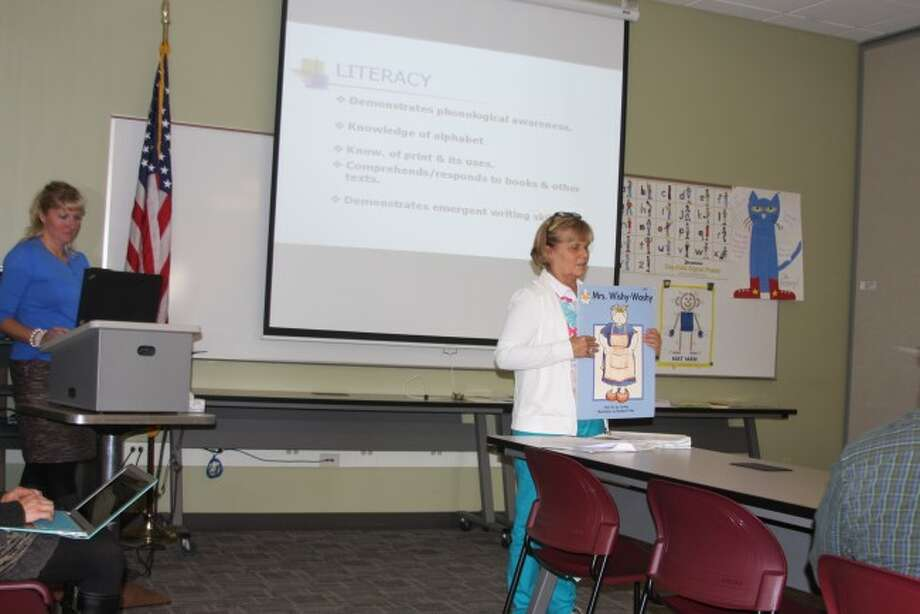 Manistee Intermediate School District preschool teacher Cathy Janowiak makes a presentation to the board of education with the assistance of Brooke McIsaac on Tuesday. Her talk focused on preschool curriculum.