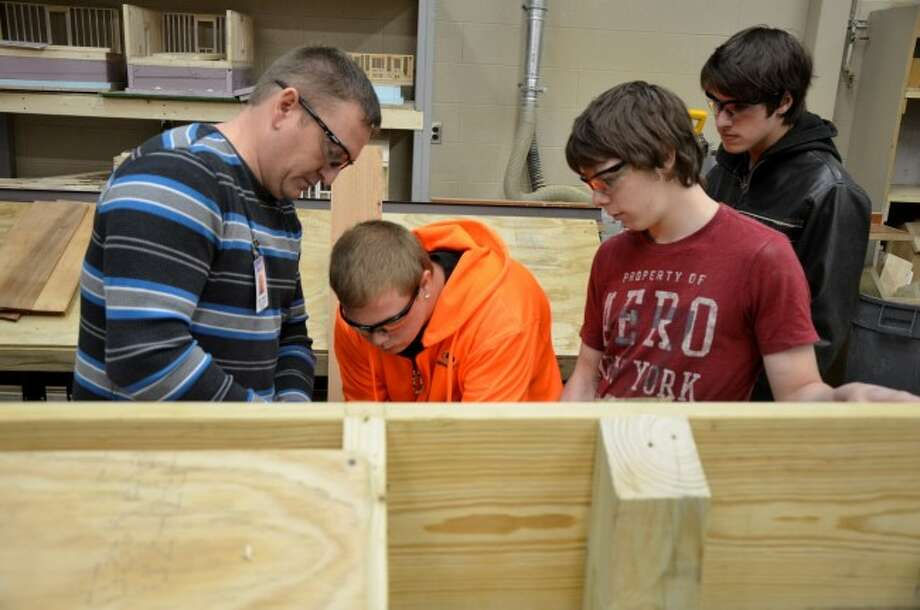 Left to right, Cadillac Technical Center applied construction technology instructor Brad VanBuren works with high school students Cody Scott of Cadillac, Marvin Dougherty of Bear Lake and Dwight Schneider of Brethren.