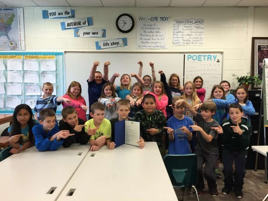 Onekama Consolidated Schools fourth graders show off a letter received from their Congressman Dan Benishek. Students were studying a unit on government and wrote to the congressman and received a response