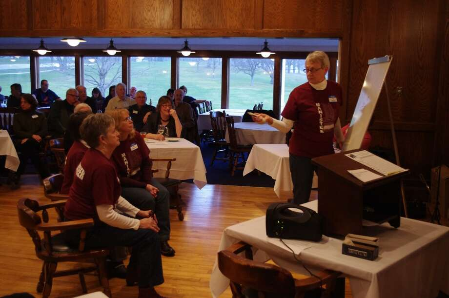 """Meg Voelker draws the picture as the """"In Vogue"""" team tries to guess the word in Friday night's Pictionary competition sponsored by the League of Women Voters of Manistee County. (Dave Yarnell/Staff Writer)"""