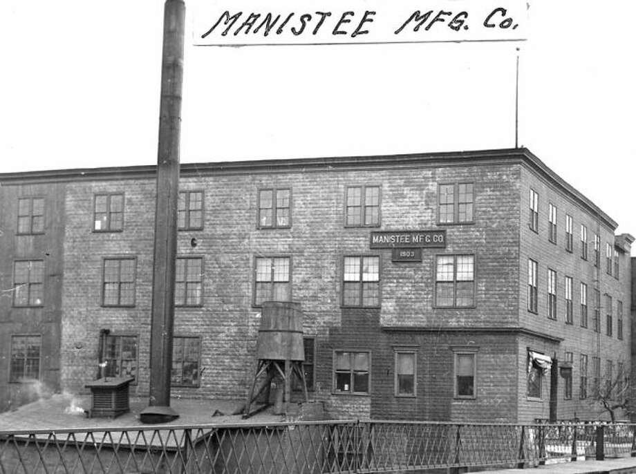The Manistee Manufacturing Company that produced furniture in the early 1900s and was located in the spot where condominiums currently exist next to the Maple Street Bridge is shown in this photograph.