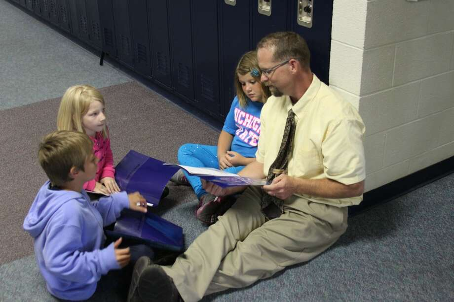 Jim Wojciechowski took over as principal at the Brethren Schools after spending the last 17 years as a teacher. The new principal is shown talking with some some the elementary students last week.