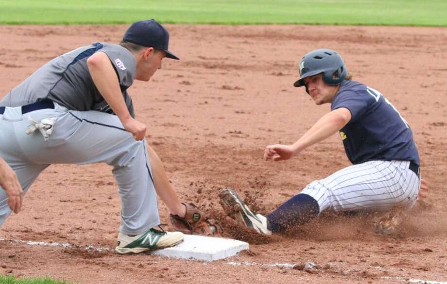 Manistee's Lucas Richardson slides into third base during the Saints' 6-4 win over the Oil City Stags on Saturday.