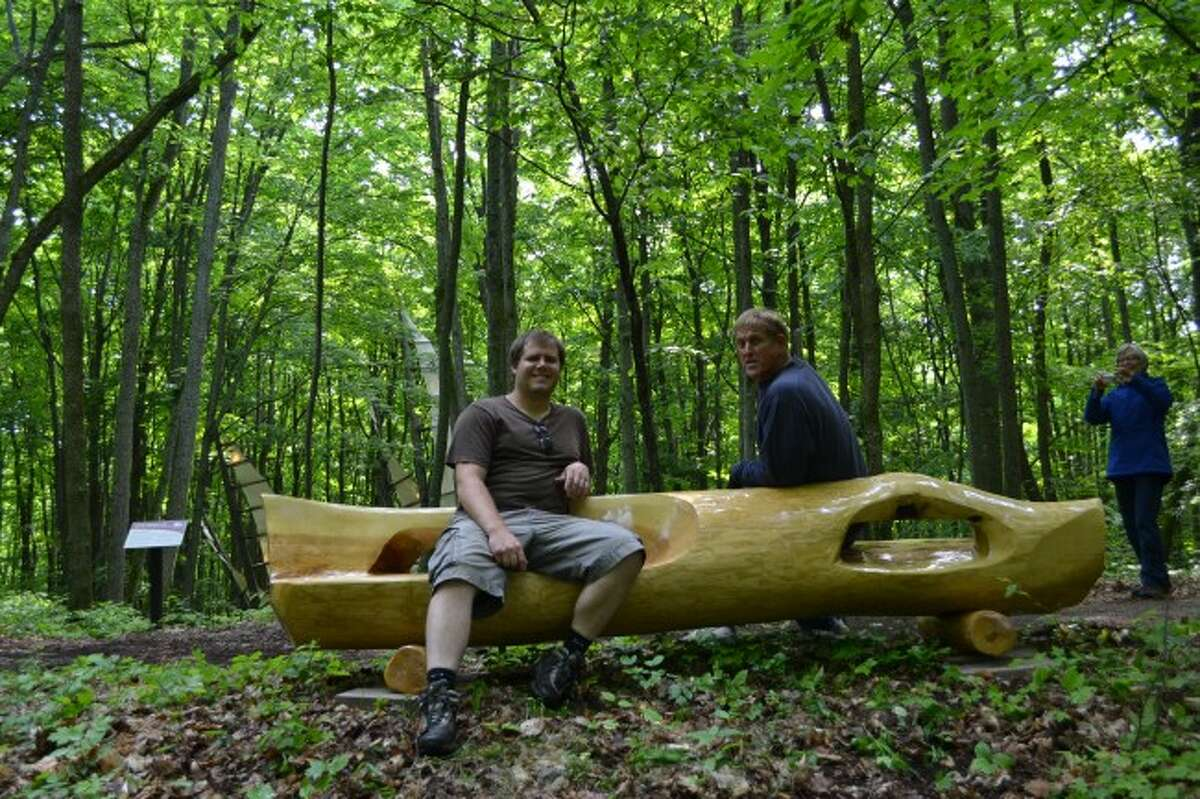 Sam Soet and Bart Ingraham rest on Soet's bench after installing their wood benches at Michigan Legacy Art Park last week. Ingraham's wife Gail is in the background along with the park's Five Needles sculpture.