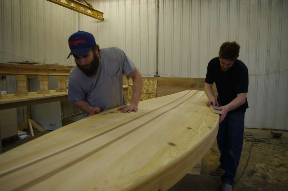 Most of the work on the custom wood paddle boards is done by hand. Partners Mike Iseringhausen (left) and Ken Scarpace sand a board, which is the second one they've built. (Dave Yarnell/News Advocate)