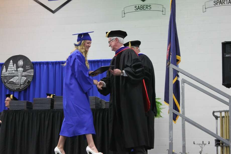 West Shore Community College President Charles Dillon presents a proud graduate her diploma. Diplomas and certificates were presented to 140 graduates at commencement exercises on Friday.