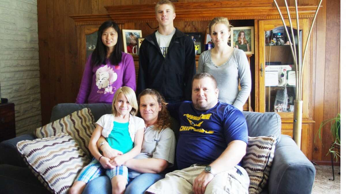 WELCOME HOME:The Codden family had to adjust to life without mother Janeen for a year while she was deployed to Afghanistan. The family is pictured (from left to right, seated) Raegan, Janeen, Chris, (standing) Ellen, Haydon and Hayleigh. Ellen is an exchange student from China. (Dave Yarnell/News Advocate and courtesy photos)
