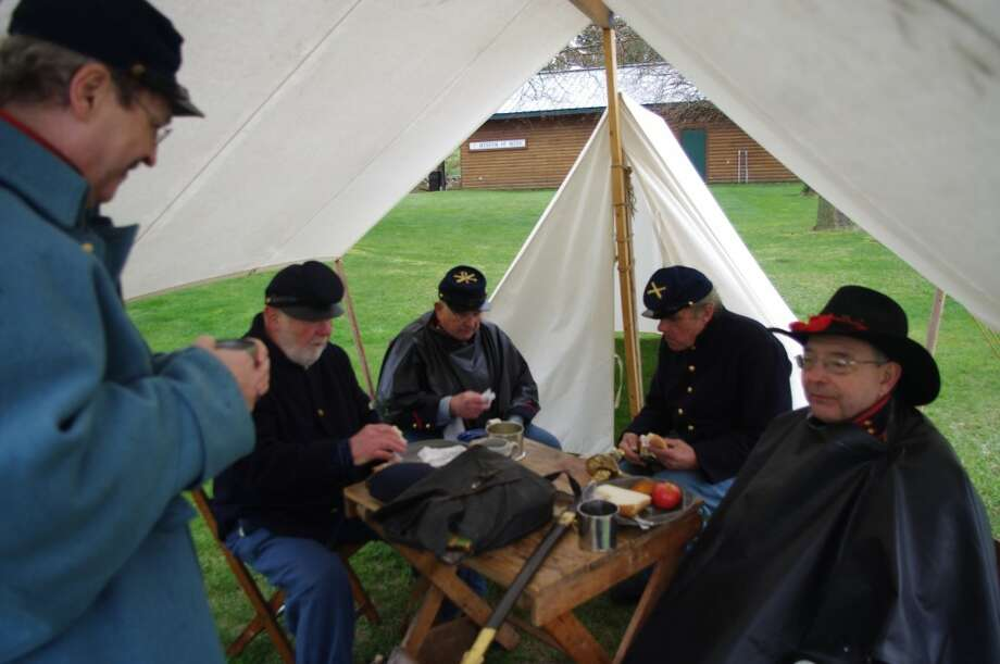 Battery D, 1st Michigan Light Artillery Civil War re-enactors, have lunch in one of the tents on Saturday afternoon at White Pine Village near Ludington. (Dave Yarnell/News Advocate)