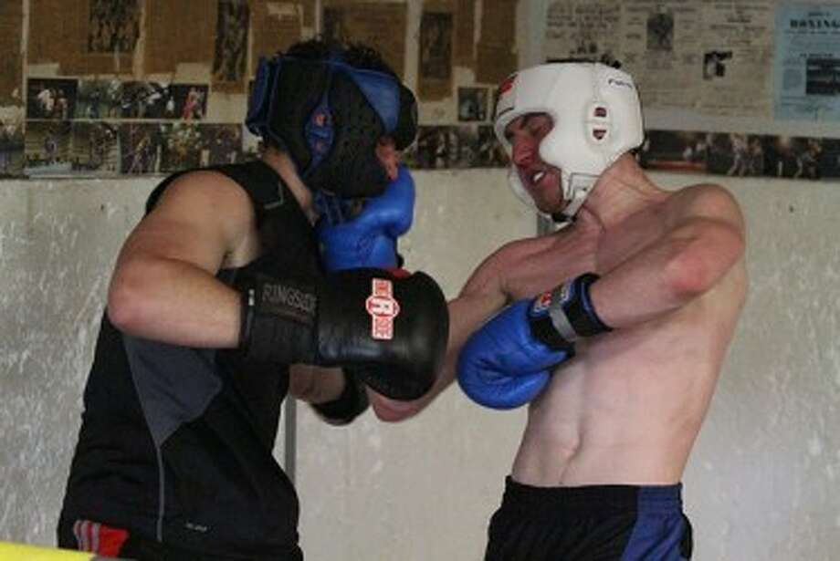 Tyler Bussell (right) connects on an uppercut during a recent sparring session with his older brother Travis. Tyler will compete this week in the Golden Gloves Tournament of Champions in Salt Lake City. (Matt Wenzel/News Advocate)