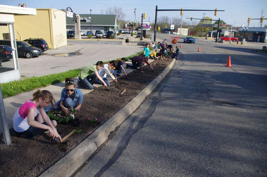 Students from Kennedy Elementary School were busy planting petunias along U.S. 31 for Manistee's Blossom Boulevard on Tuesday. (Dave Yarnell/News Advocate)