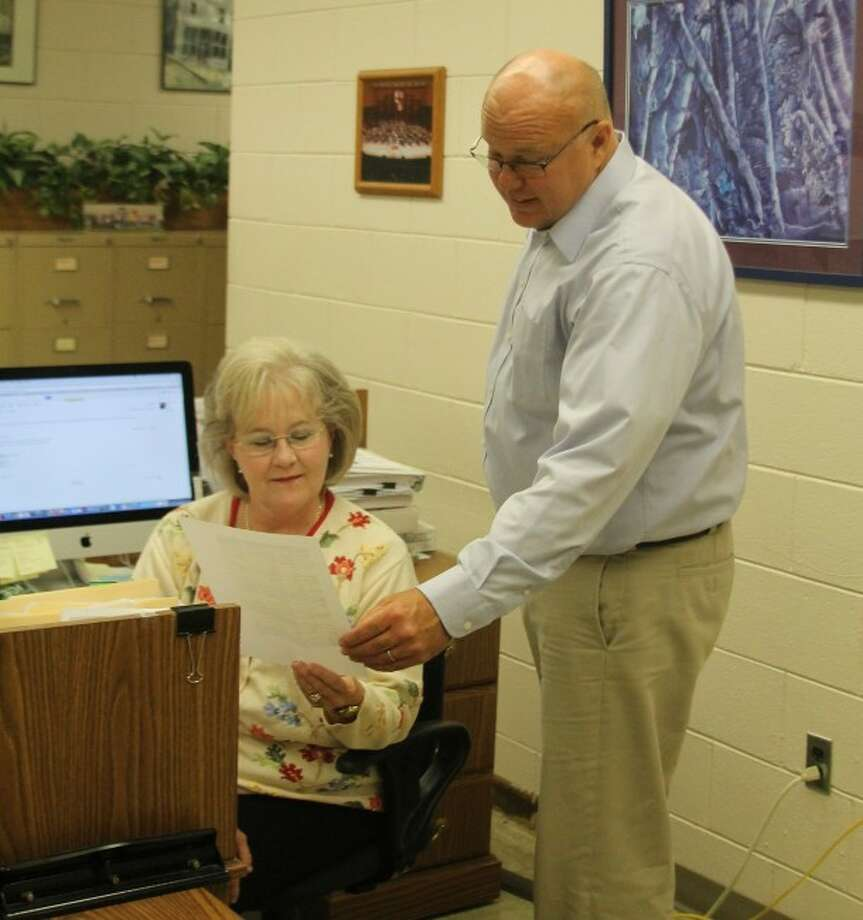 New Manistee Area Public Schools superintendent Ron Stoneman first day on the job was Wednesday. Stoneman is show going over his schedule with administrative assistant Nancy Day.
