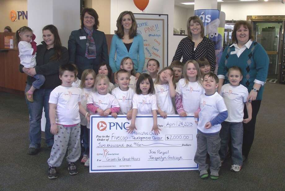 Jackie Gielczyk and Joni Purgiel of PNC present a check for $2,000 to the class from FiveCAP's Manistee Child Development Center. Gielczyk and Purgiel earned the grant by volunteering at the center a minimum of 40 hours during a 12-month period through the bank's Grow Up Great program.