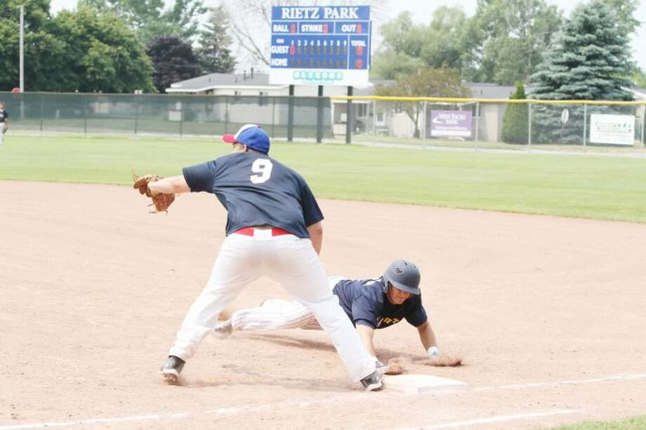 Andy Fortier dives back to first on a pickoff attempt in the Saints' sweep of the Mayville Bad Boys in a doubleheader on Sunday.