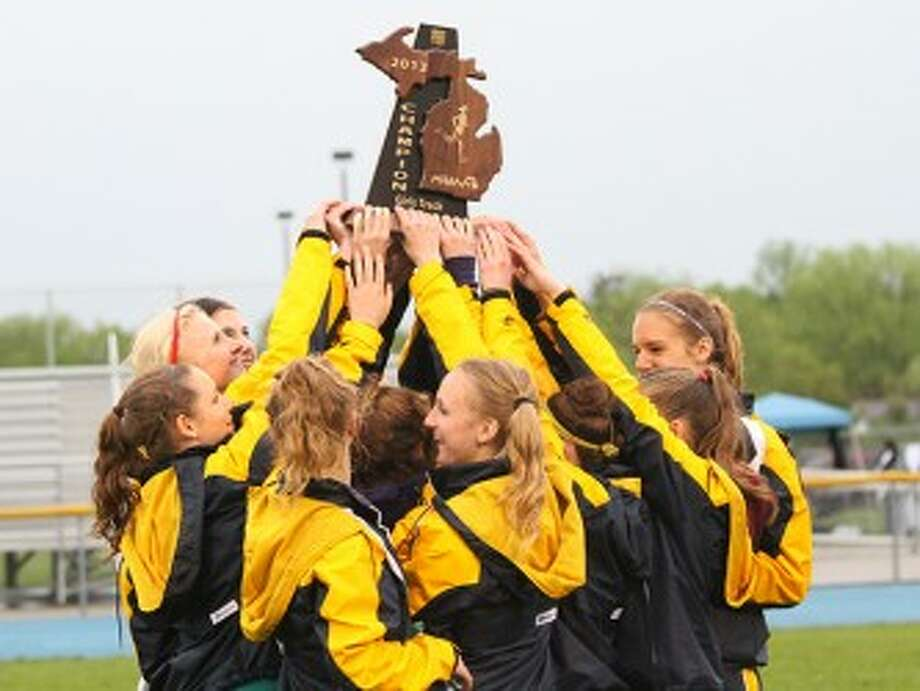 The Manistee girls track and field team hoists the Division 3 regional championship trophy on Friday at Mason County Central. (Matt Wenzel/News Advocate)
