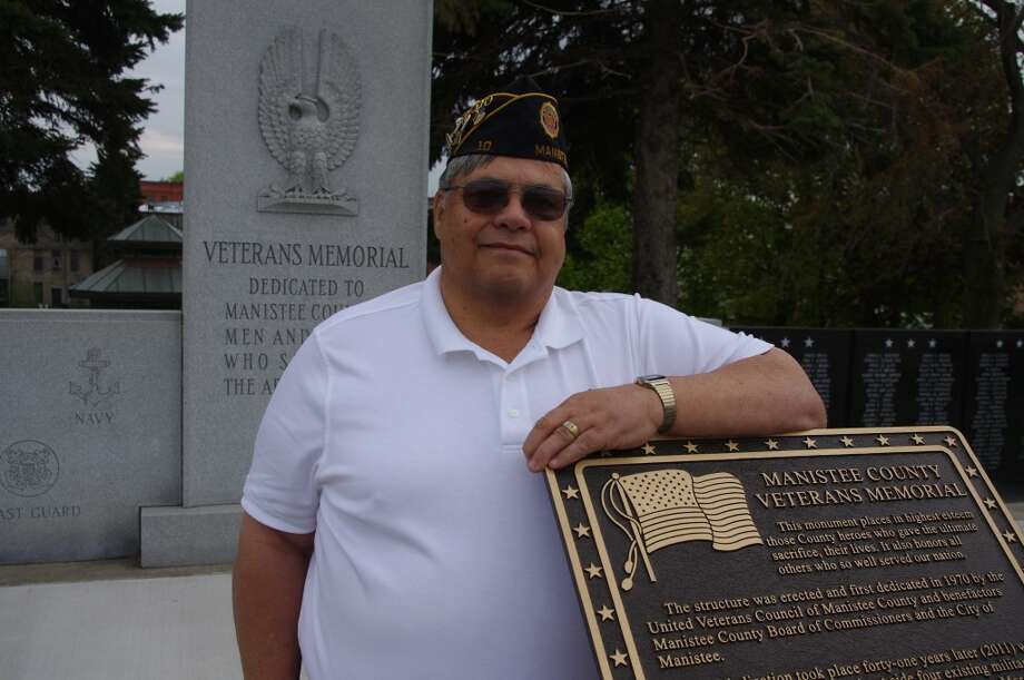 """Keith Graham, chair of the United Veterans Council of Manistee County, at Veterans Memorial Park in Manistee. The plaque acknowledges the role the veterans council and other organizations played in improvements to the park and says, in part, """"Take a moment to pause and reflect. Freedom is never free. Value our veterans and the men and women protecting our country today. Cherish and revere the memory of those who died in combat and of our POWs and MIAs."""" (Dave Yarnell/News Advocate)"""