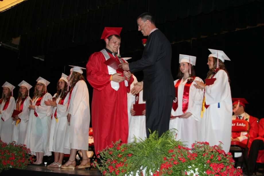 Bear Lake Schools Board of Education president Charles Brooks presents a diploma to Gary Foster at Friday's commencement exericises. A total of 21 students graduated in ceremonies held at the school gymnasium.