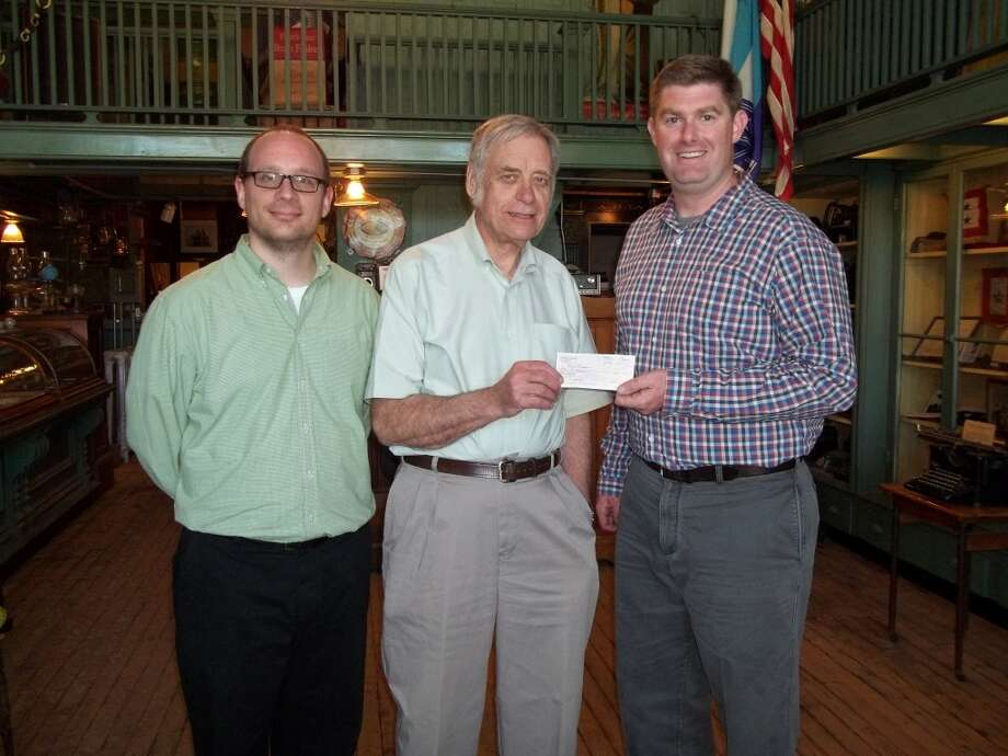 Mark Fedder and Steve Harold of the Manistee County Historical Society receive a donation check from Blarney Castle's Dennis P. McCarthy.(Courtesy photo)