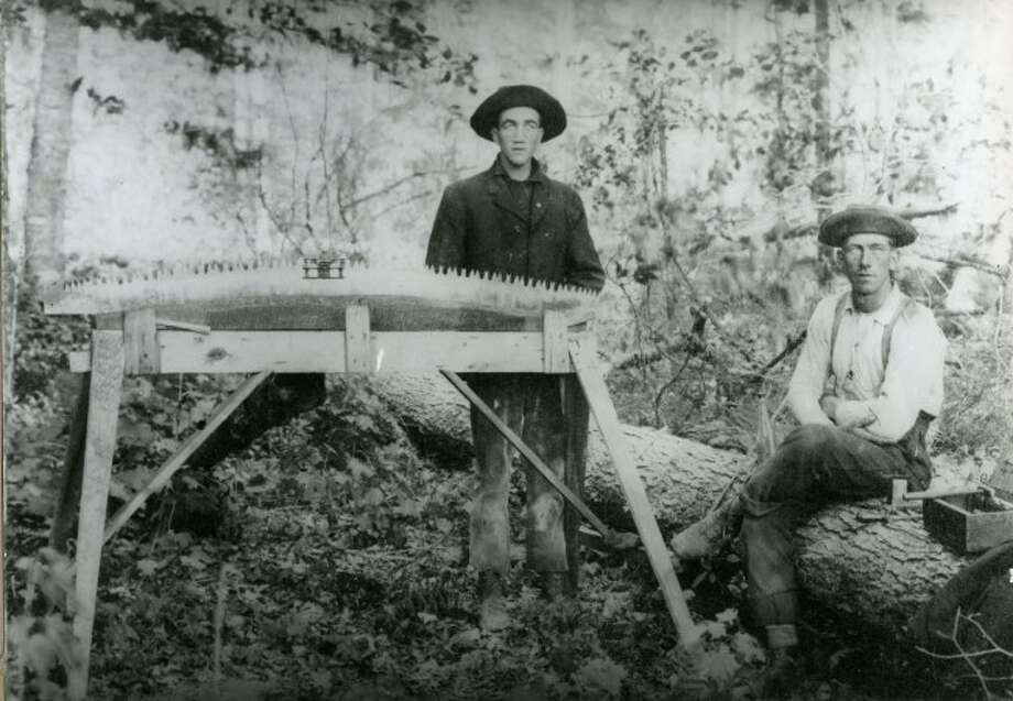 These two lumberjacks prepare to sharpen a saw blade.