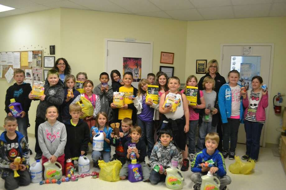 The third grade class from Kaleva Norman Dickson School gathers at Homeward Bound Animal Shelter with items they donated Thursday: laundry soap and bleach, animal food and toys. (Meg LeDuc/News Advocate)